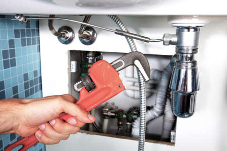 Plumbing work and sanitary engineering repairing a pipe under a sink. Sanitary works. Plumber repairing Stock Photo
