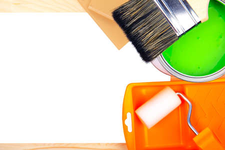 paintroller: Colorful bucket of green paint with paintroller in tray and a white sheet of paper for text on a wooden background