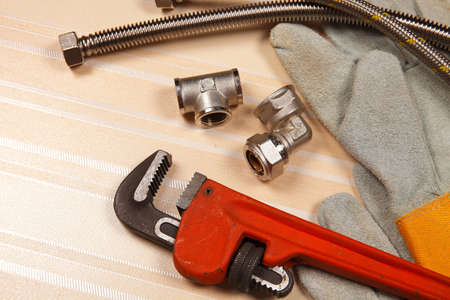 Set of plumbing and tools on the table. Fitting, suede gloves and red adjustable wrench for plumbing works