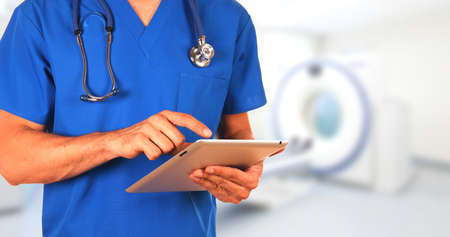 tomograph: Closeup confident medical doctor with stethoscope and tablet standing  isolated on hospital background with tomograph