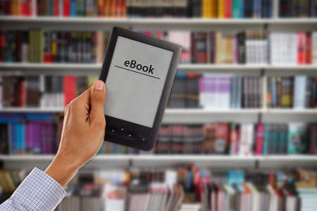 shelfs: Mans Hand holding empty e-book reader with library shelfs in background Stock Photo