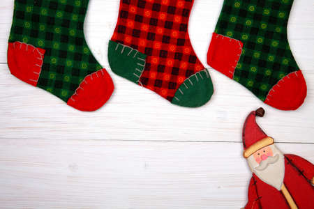 wooden toy: Christmas stocking on white wooden background and toy sana claus under