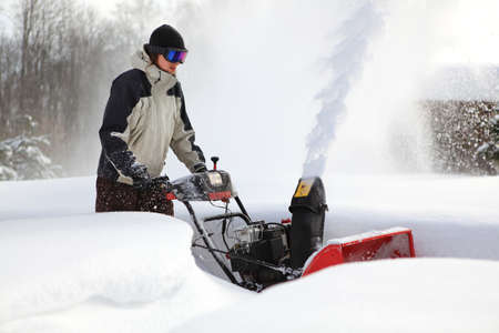 A man works snow blowing machine