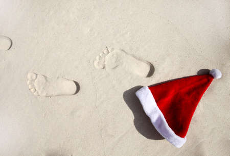 trace: Santa hat and his trace on a beach Stock Photo