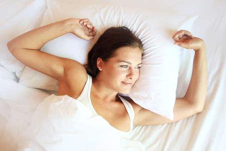 despertarse: Joven y bella, mujer que despierta descansado plenamente.