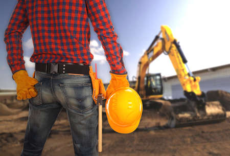 worksite: Perspective view of male engineer standing on worksite holding yellow helmet and inspecting construction