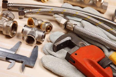 aguas residuales: Conjunto de fontanería y herramientas sobre la mesa. Montaje, guantes de gamuza y una llave ajustable para trabajos de plomería