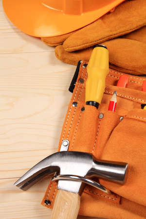 carpenter vise: Hammer, pliers, helmet, red pencil, work gloves and other tools isolated on a wooden background Stock Photo
