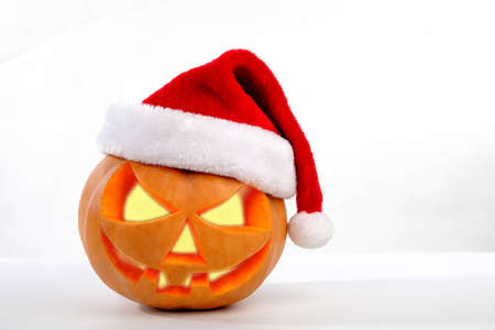 Spooky halloween pumpkin Jack O Lantern shiny inside wearing christmas hat on white background
