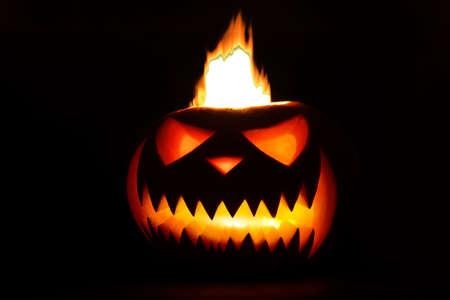 Spooky halloween pumpkin Lantern shiny inside on black background