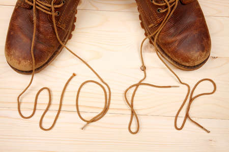 Pair of work boots. There written the word work by laces on wooden background