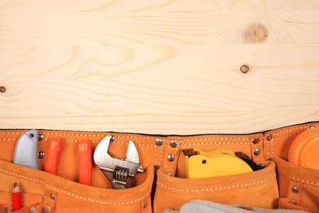 suede belt: Suede orange belt with pliers, red pencil, work gloves and other tools isolated on a wooden background