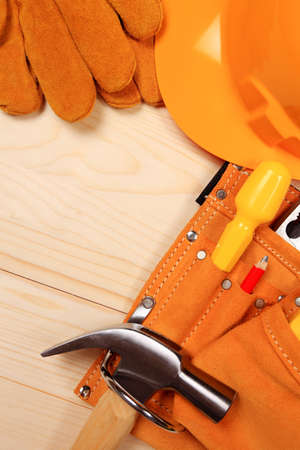 Hammer, pliers, helmet, red pencil, work gloves and other tools isolated on a wooden background Stock Photo