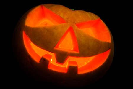 daemon: Spooky halloween pumpkin shiny inside on black background Stock Photo