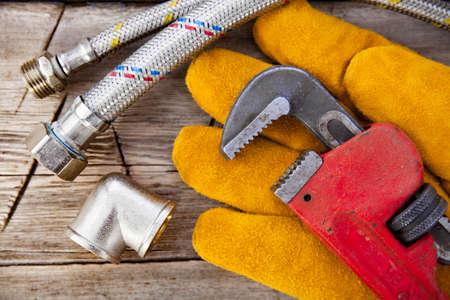 alicates: Conjunto de plomería y herramientas sobre la mesa. Ajuste, guantes de gamuza y llave ajustable para trabajos de plomería