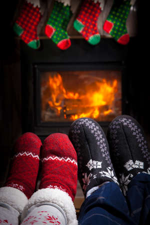 fireplace family: Christmas concept - family in front of fireplace. Two pairs of ornamented Christmas socks.