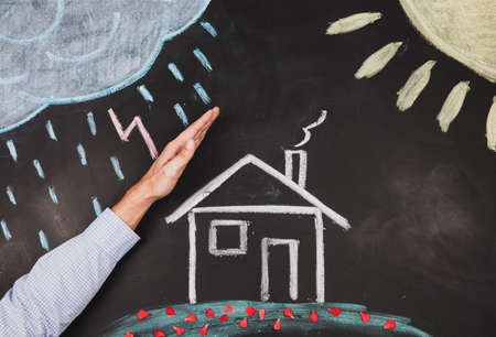 protecting your business: Businessman hand protects a house from rainy weather Stock Photo