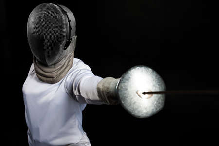 swordsman: Portrait of fencer woman wearing white fencing costume practicing with the sword. Isolated on black background.