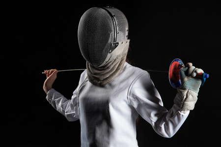 Portret van schermersvrouw die het witte schermende kostuum dragen uitoefenend met het zwaard. Geïsoleerd op zwarte achtergrond.