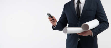 Portrait of a architect looks at smartphone on light gray background Stock Photo