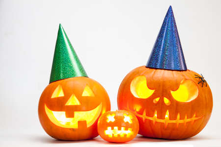 Three Halloween pumpkin head jack lantern with burning candles isolated on white background