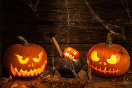 Two Halloween pumpkin head jack on dark wooden background