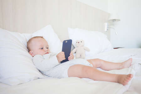 Adorable toddler baby girl sitting on the sofa and playing with smartphone. Stock Photo