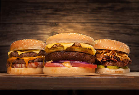 Three large burgers on wooden background. Low angle front view. Copy space for your text. Reklamní fotografie