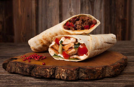 burrito and shawarma wraps with beef and pork vegetables on wooden table