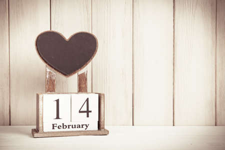 Valentines Day card with wooden block calendar on white wooden background witn copy space for text. Reklamní fotografie
