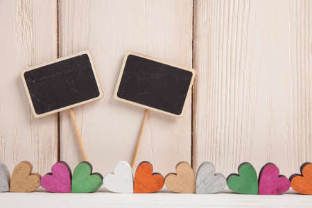 Valentines day concept. A colorful hearts and two black plank for text on a white wooden background.
