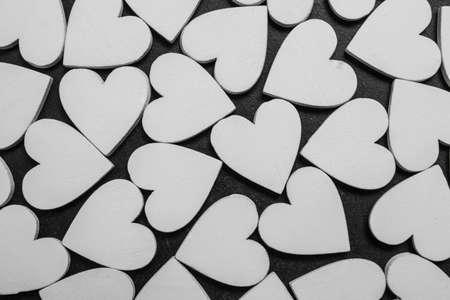 White wooden hearts on black background. Valentines pattern.