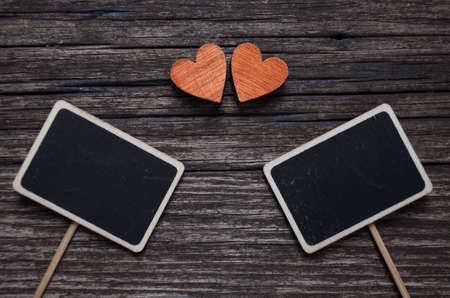 Valentines day concept. Two red hearts and two black plank for text on old wooden background.