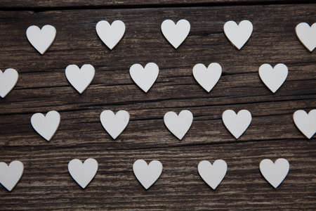Valentines day card. A white hearts on old wooden background. Valentines pattern.