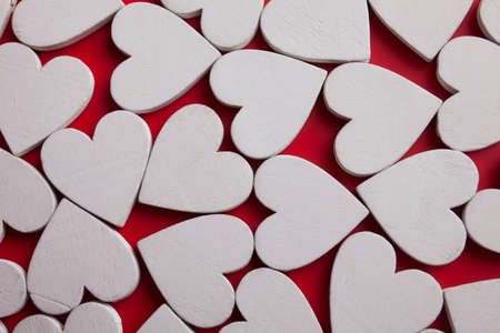 White wooden hearts on red background. Top view Valentines pattern.