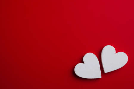 Two white wooden hearts on red background. Top view Valentines pattern. Reklamní fotografie
