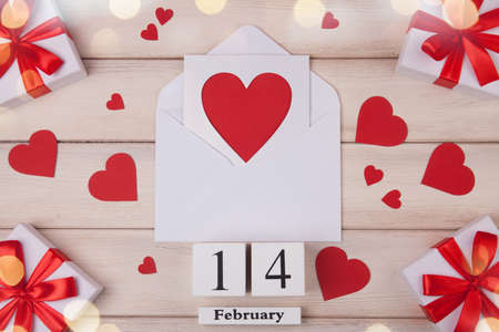 Wooden white background with red hearts, gifts, love envelope and wooden block calendar. The concept of Valentine Day. Top viev.