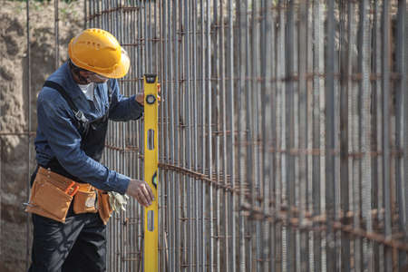 worker checks the construction parameters of foundation