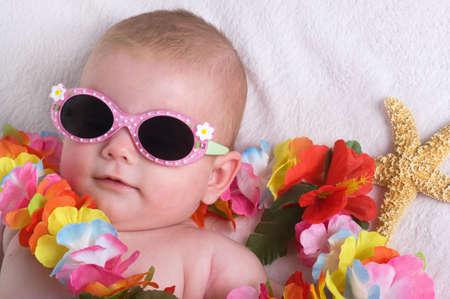 Beautiful baby girl with lei, sun glasses and a starfish on vacation