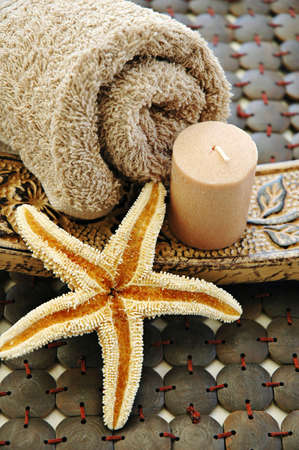 Brown towel, starfish and candle on a wooden mat Imagens