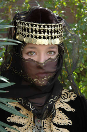 A girl wearing a black veil and head dress with golden adornments