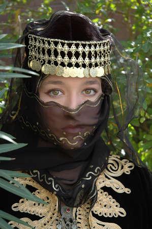 Een meisje draagt een zwarte sluier en hoofd jurk met gouden versieringen
