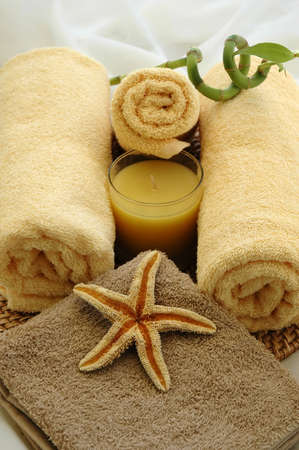 Yellow towels, starfish, bamboo plant, and candle in a massage studio Stock Photo - 664307
