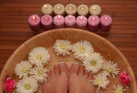 A pair of pedicured feet in a bowl full of water, pebbles, and various fresh flowers