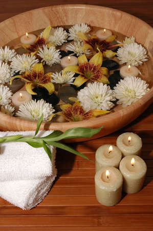 Various flowers, pebbles, floating candles in a bowl of water (Towels, candles and bamboo plant on a bamboo mat) Stock Photo - 665924