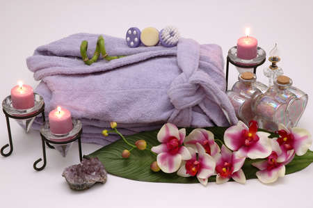 Bathrobe, orchid, perfume bottle, bath salt, skin brushes, sponges and candles in a spa Zdjęcie Seryjne