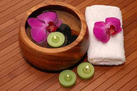 Floating green candles, orchids, towels on a bamboo mat Stock Photo