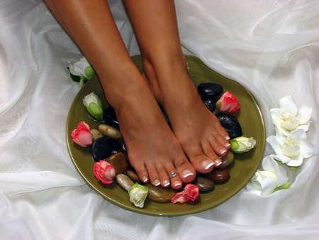 A pair of pedicured feet on silk cloth Reklamní fotografie