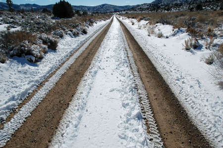 Long snowy dirt road in Nevada desert photo
