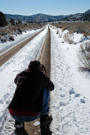 Photographer taking picture of long snowy road photo